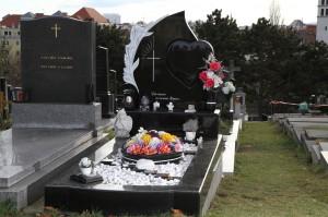 Schwarzes Grab mit Grabstein in Segelform mit einem Herz und weißen Kieselsteinen