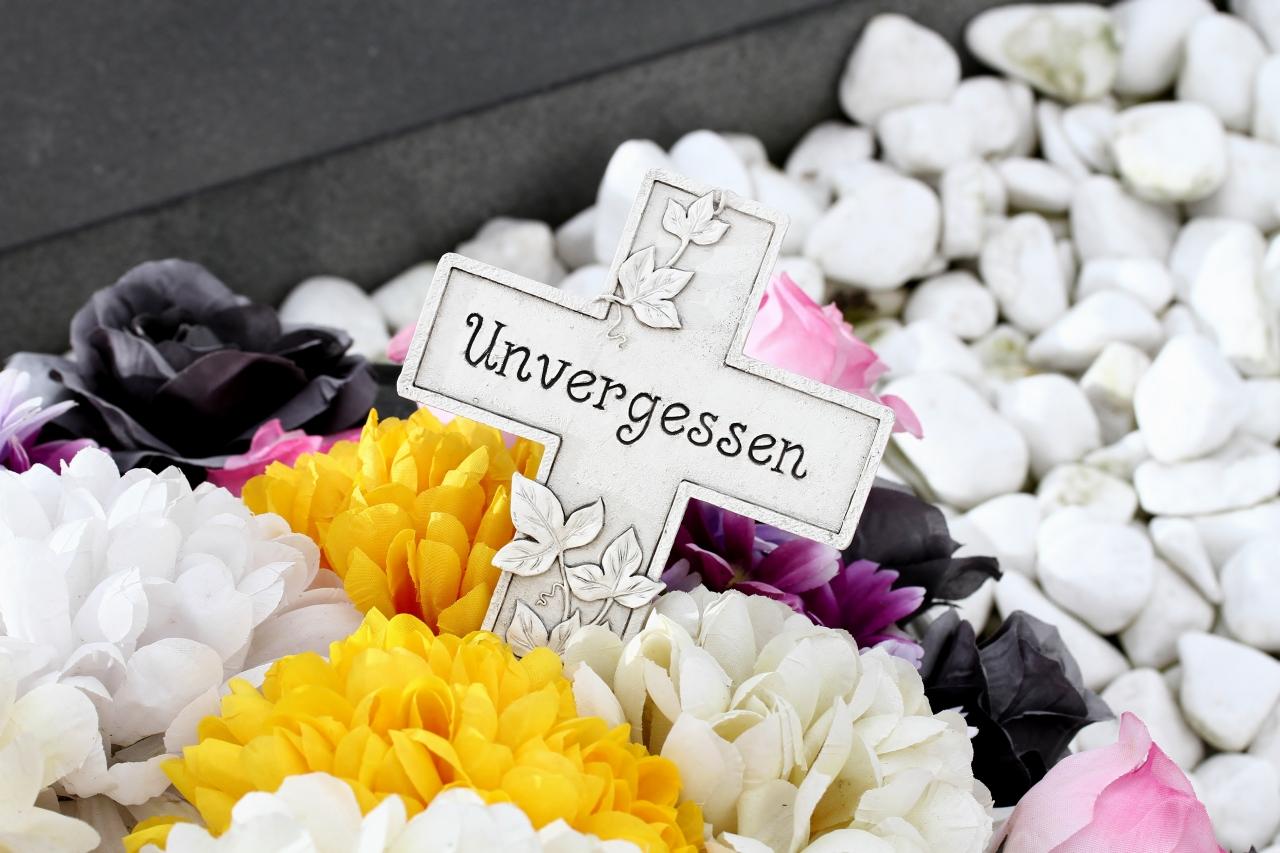 Unvergessen auf weißem Kruzifix mit Blumenschmuck